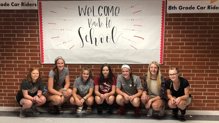 Members of National Jr. Honor Society in front of a welcome back bulletin board