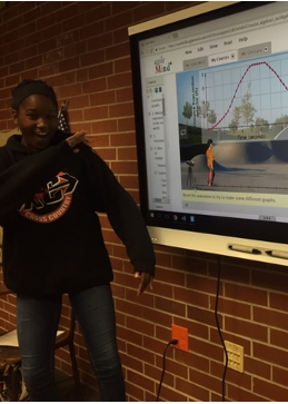 Student in front of the Smart Board showing her graph presentation.