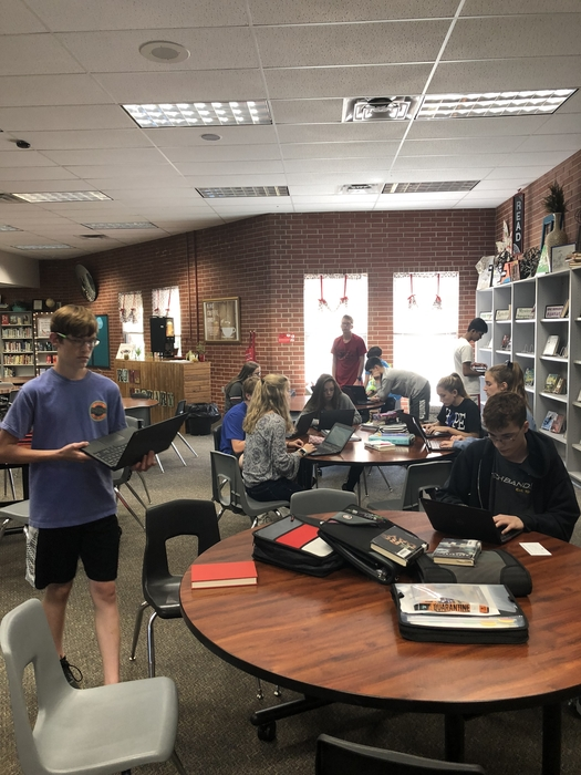 Students are working on laptops in the library