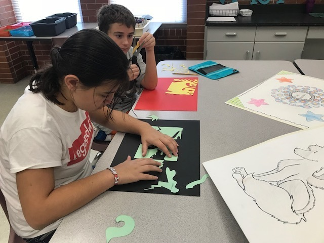 Students cutting paper and working in art class.