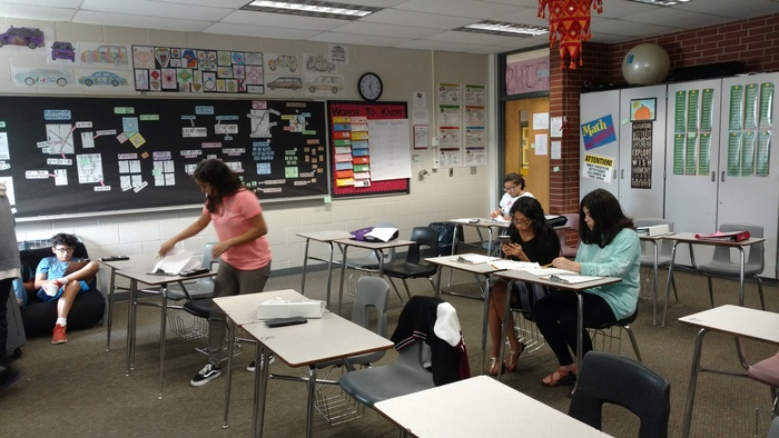 Students standing and sitting at desks in a math classroom.