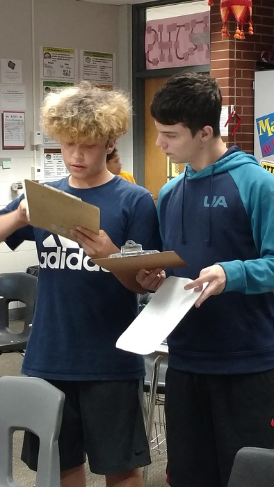 Two boys working on clipboards in math class.