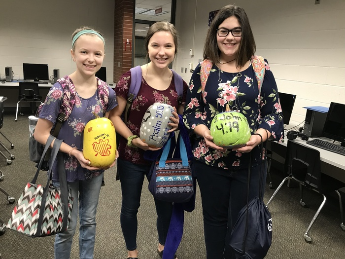 Students holding decorated pumpkins with scriptures on them.