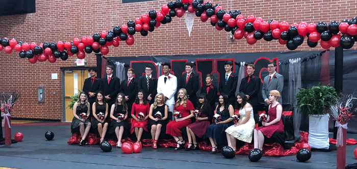 Girls and boys dressed up and sitting in front of homecoming decor.