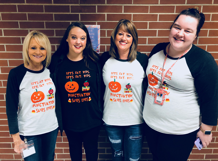 English teachers posing with funny Halloween shirt on.