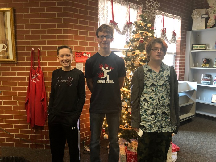 Students who won the Spelling Bee standing in front of a Christmas tree.