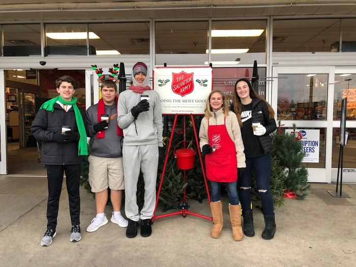 Students standing in front of a store ringing bells for the Salvation Army.