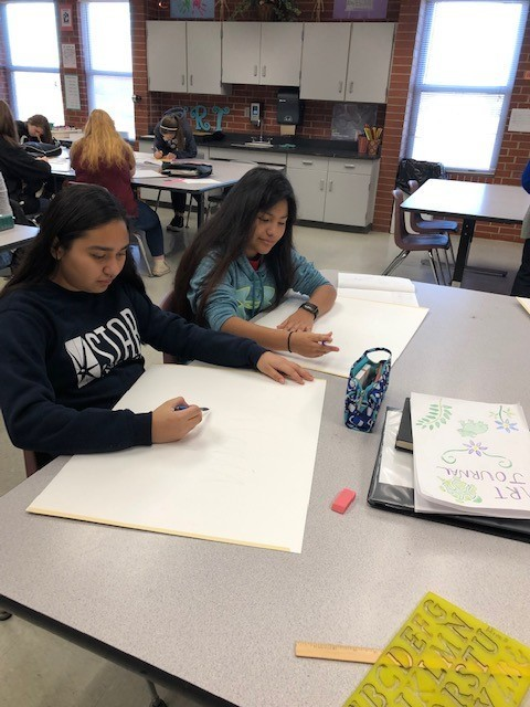 8th grade students siting at a large table working on tracing.