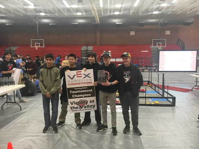 Robotics team standing with their awards in a gym.