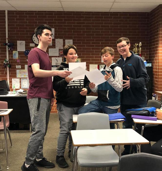 Students standing in front of the class in a group reading a script.