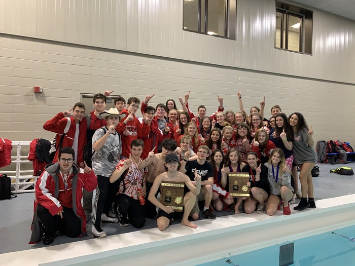 Boys and girls swim and dive teams posing next to the pool holding their trophies.
