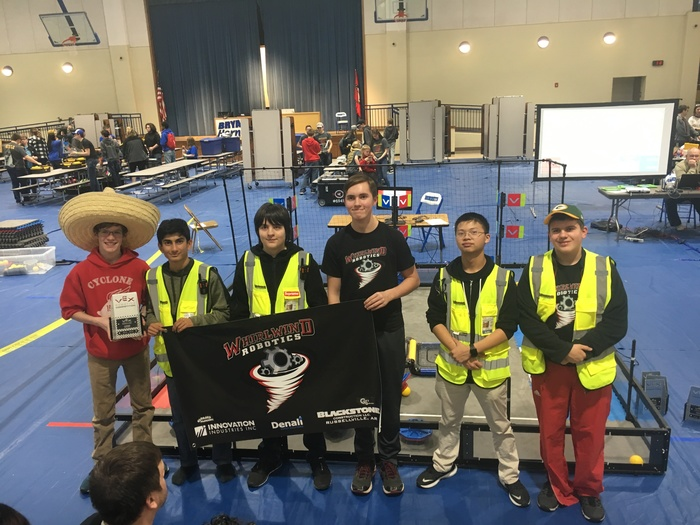 Robotics team posing with their trophy at the robotics tournament.