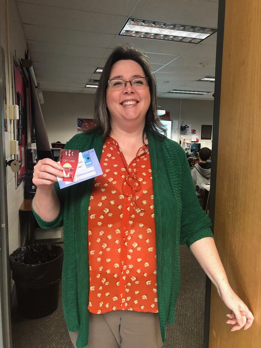 Kim Moore posing with her gift card she won.
