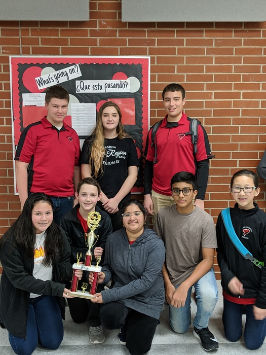 Quiz Bowl team posing in two lines with their second place trophy.