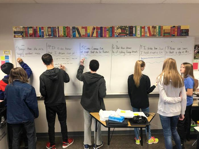 4 students writing on white board, standing in a row at the front of the class.