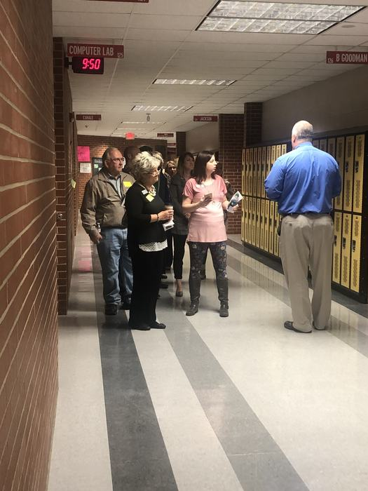 Mr. Kordsmeier stands in the hall and explains what is happening in a class to a group of adults.