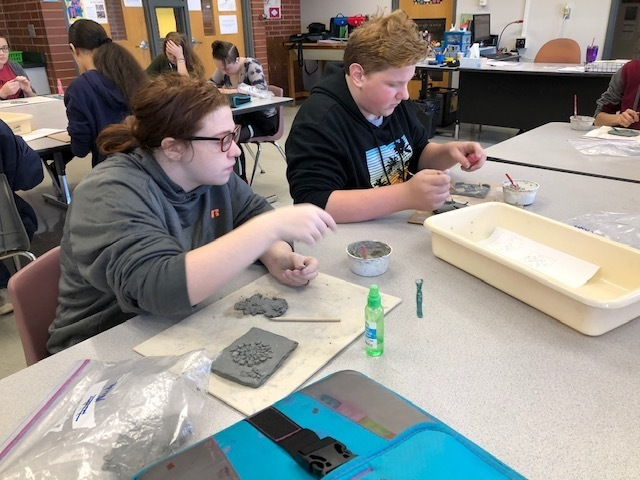 Students molding and cutting clay to create their artwork.
