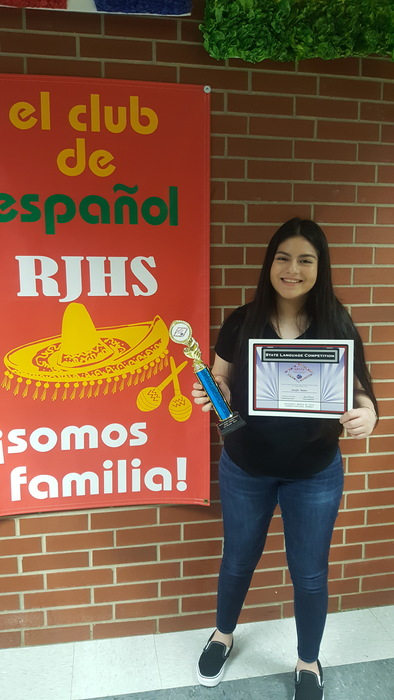 Student standing holding a trophy in front of the Spanish club banner.