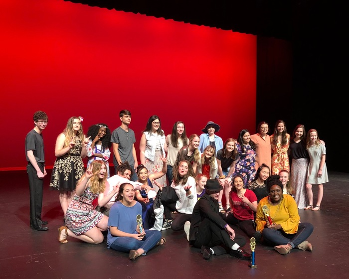 Talent show acts grouped together for a picture on the stage.