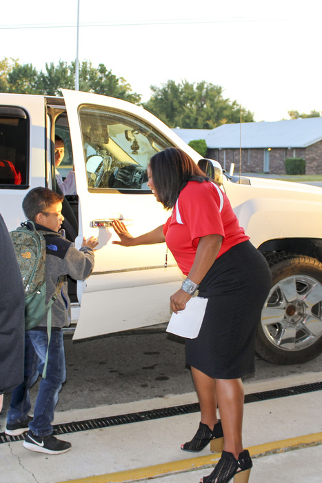 Mrs. Jackson helps a student out of their car during morning drop off at Crawford Elementary.