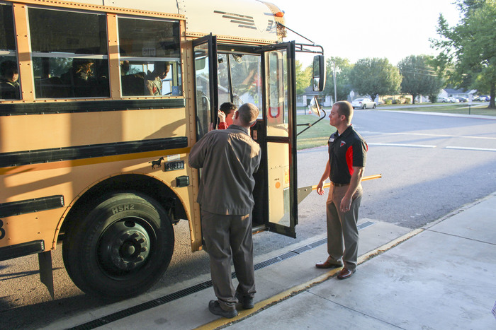 School board president Chris Cloud and Mr. Robertson help students off the bus at Crawford Elementary during morning drop off.