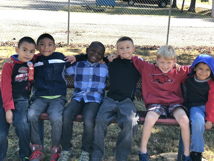 picture of kids sitting on a bench enjoying the nice weather at recess