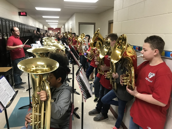 band and choir students caroling in the hallways