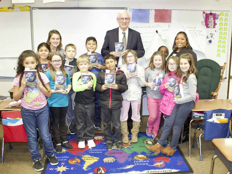 Group of third grade students holding dictionaries in a classroom.