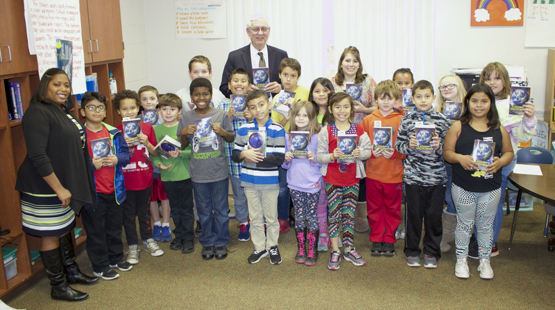 John Bynum of the Russellville Downtown Rotary Club presents dictionaries to a group of third grade students at Crawford Elementary.