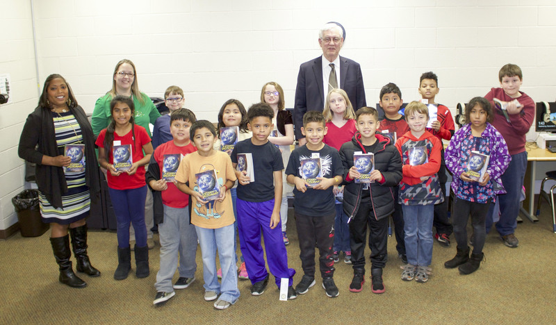 John Bynum of the Russellville Downtown Rotary Club present dictionaries to third grade students at Crawford Elementary.